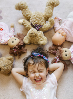 Portrait of laughing little girl lying on the floor with teddies and dolls around her - MGOF001445