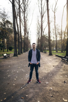 Young man standing in the park with hands in his pockets - MGOF001448