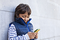 Portrait of boy leaning against wall looking at his smartphone - VABF000162