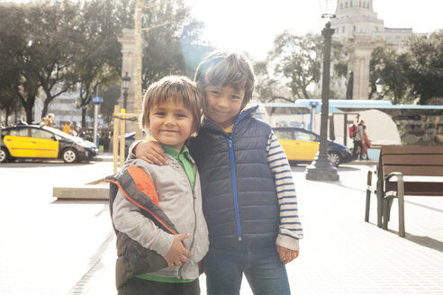 Spain, Barcelona, portrait of two little brothers standing arm in arm at backlight - VABF000165