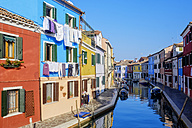 Italy, Veneto, Burano, view to colourful row of houses with drying laundry at sunlight - HAMF000147