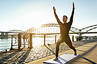 Germany, Cologne, Young man practicing yoga at the riverside - MADF000811