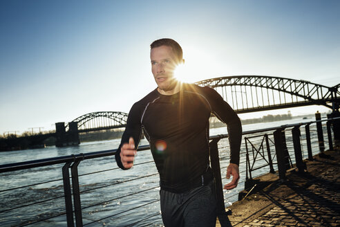 Germany, Cologne, Young man running at the riverside - MADF000814