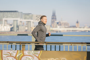 Germany, Cologne, Young man running at the riverside - MADF000817