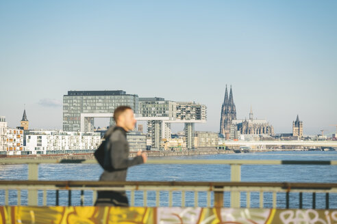 Germany, Cologne, Young man running at the riverside - MADF000820
