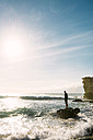 Spain, Fuerteventura, La Pared, silhouette of a man standing on a rock looking at horizon - GEMF000728