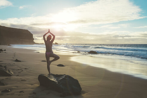 Spain, Fuerteventura, El Cotillo, back view of woman practicing yoga on the beach at sunset - GEMF000734