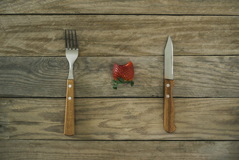 Fork, knife and a bitten strawberry on wood - JPF000115