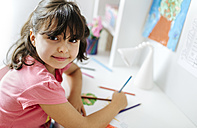 Portrait of little girl drawing on his desk at home - MGOF001454
