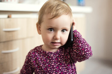 Portrait of blond toddler playing with smartphone - HAPF000232
