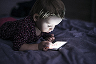 Toddler lying on  bed playing with smartphone - HAPF000238