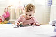 Toddler playing with digital tablet on bed - HAPF000241