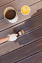 Woman's hand applying glaze with brush on floorboards - GWF004630
