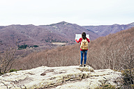 Spain, Barcelona Province, Sants Fe del Montseny, woman with backpack and map in the mountains - GEMF000740