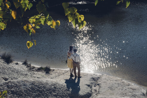 Back view of lovers standing at water edge - MJF001709