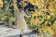 Portrait of dancing young woman with bouquet in autumnal nature - MJF001715