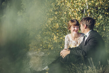 Happy bridal couple sitting face to face in nature - MJF001718