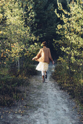 Back view of old-fashioned styled woman with storm lamp walking on a path - MJF001724