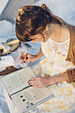 Woman with glass of champagne reading a book - MJF001730