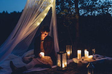 Happy woman in a romantic camp in autumnal nature by candle light - MJF001739
