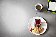 Digital tablet, cup of coffee and croissant - FMKF002275