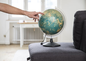 Hand pointing on globe on couch - FMK002278