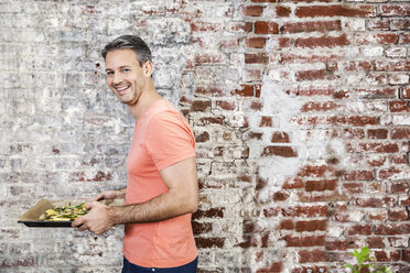 Man carrying baking tray with potato wedges - FMKF002326