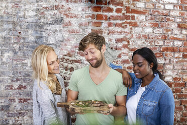 Portrait of smiling man with two women holding board with steak - FMKF002332