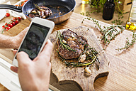 Man taking celll phone picture of prepared steaks - FMKF002335