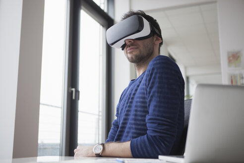 Smiling man wearing Virtual Reality Glasses in the office - RBF004086