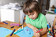 Little boy drawing on blue paper at home - VABF000178
