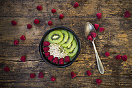 Bowl of kiwi apple rocket smoothie with chia seed, popped amarant, kiwi slices and raspberries - LVF004555