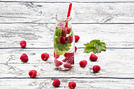Glass bottle of infused water with raspberries and mint - LVF004558