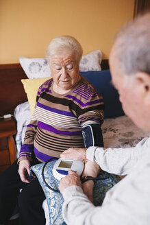 Senior man checking blood pressure of his wife at home - GEMF000743