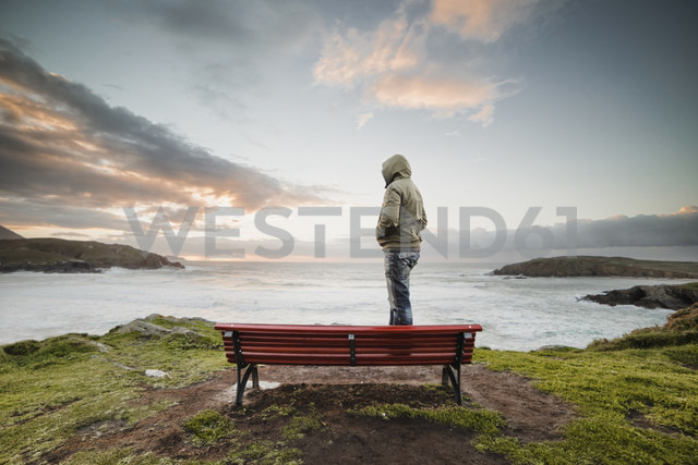 Spain, Ferrol, man wearing hooded jacket standing on a bench at the coast looking at distance - RAEF000904