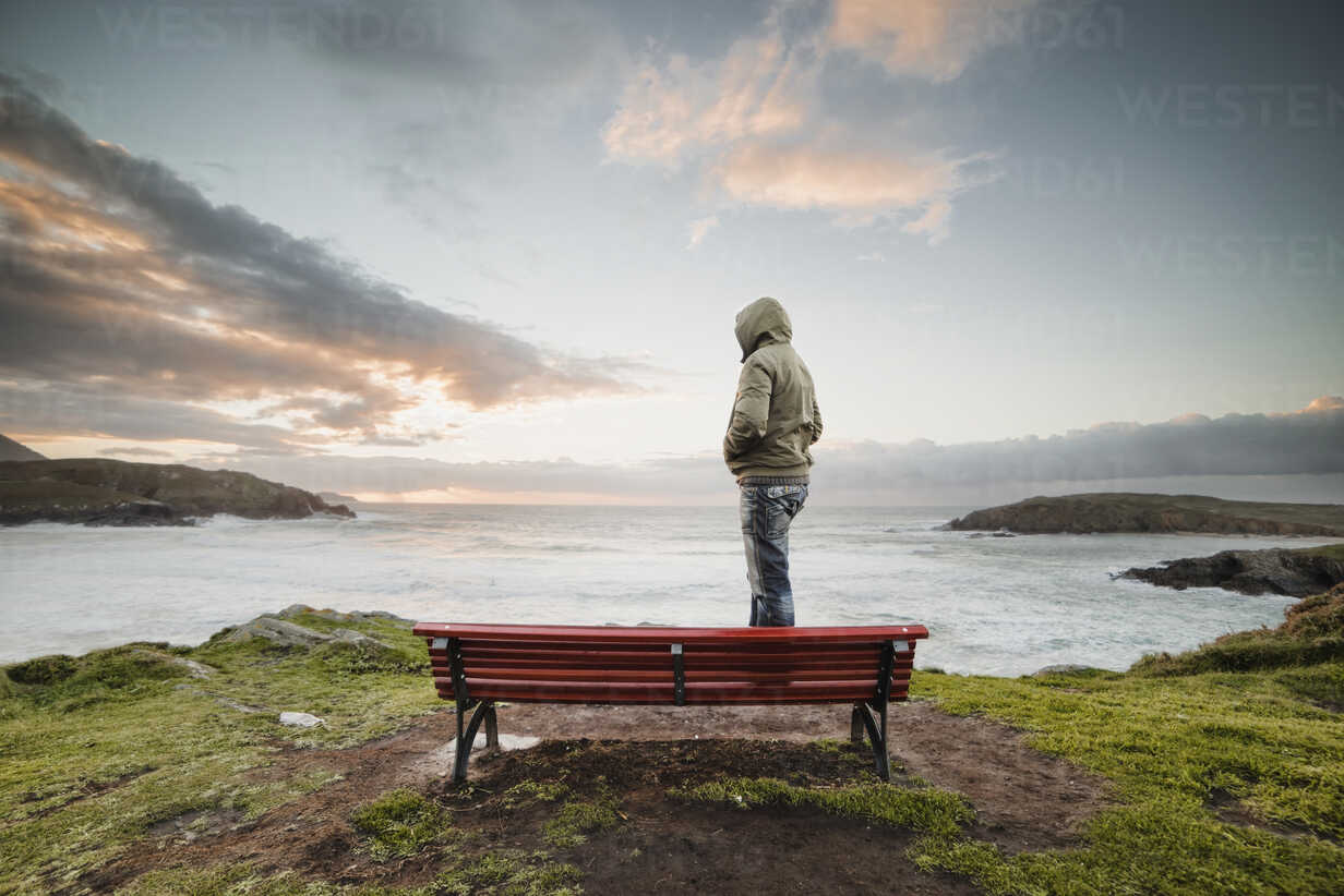 Spain, Ferrol, man wearing hooded jacket standing on a bench at the coast looking at distance - RAEF000904 - Ramon Espelt/Westend61