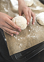 Boy's hands putting raw wheat roll on backing paper - DEGF000656