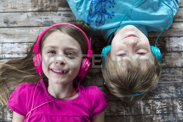 Portrait of brother and little sister hearing music with headphones - SARF002579