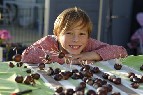 Portrait of happy little boy with tinkered chestnut figurines - LBF001390