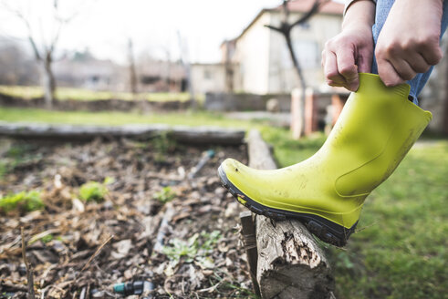 Woman putting on her Wellington boots in the garden, close-up - DEGF000659