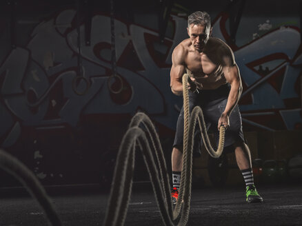 Mature crossfit athlete exercising with ropes - MADF000829