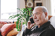 Portrait of smiling senior man telephoning with smartphone at home - GEMF000746