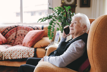 Smiling senior woman telephoning with smartphone at home - GEMF000749
