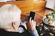 Senior woman sitting in the living room using smartphone - GEMF000752