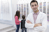Portrait of smiling optician in shop with people in background - ERLF000141