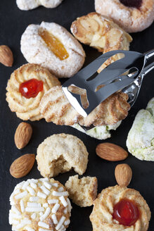Different sorts of Italian almond cookies and a pastry tong - CSF027222