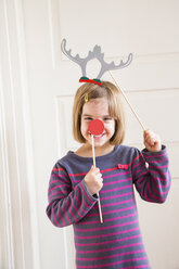 Portrait of little girl with toy antler and red nose - LVF004574