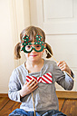 Portrait of smiling little girl with Christmas tree spectacles and toy bow - LVF004577