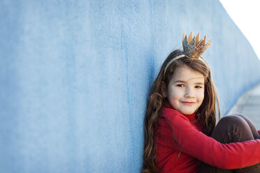 Portrait of smiling ittle girl with a crown leaning against blue wall - VABF000208