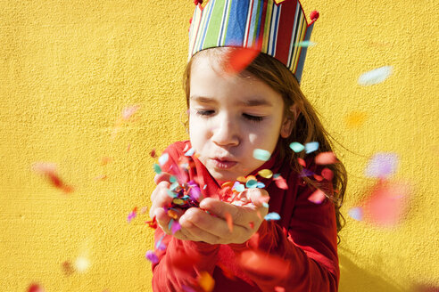 Portrait of little girl wearing paper crown blowing confetti - VABF000211